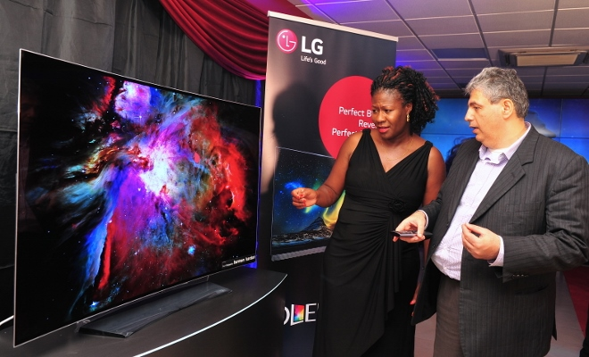 LG General Manager Marketing Moses Marji takes Edith Onyango through the features of the new TV during the launch.